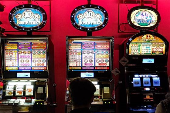 Zwei Personen vor drei beleuchteten Spielautomaten.